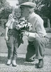 Maurice Chevalier kissing a child, holding bouquet.