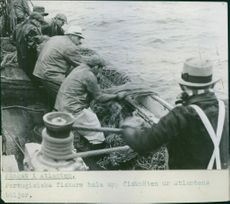 Portuguese fishermen haul up fishing nets from the Atlantic waves.