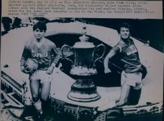 A newspaper clip by Kevin Ratcliff and Bryan Robson in front of the FA Cup