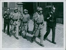Soldiers marching in street while communicating with each other and smiling.