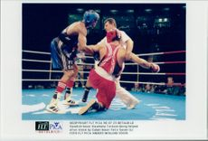 Swedish boxer Kwamena Turkson gets help getting up after a bang of Cuban boxer Felix Savon during the 1996 Olympic Games