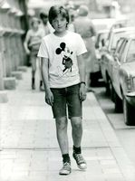 A young boy, with a sad face, wearing a shirt with Mickey Mouse print, walking on the sidewalk, looking at the camera, 1977.