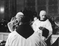 Pope Paul VI making a gesture at the crowd.
