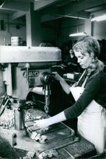 Woman worker working on drill machine in the factory. 1961