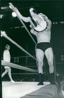 Wrestler lifted a woman and putting in the ring.