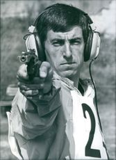 Hungarian athlete Peter Kelemen in action, pointing a pistol during a competition, 1973.