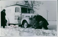 Soldier taking out the snow under the wheels of the van in Hungary during World War II.