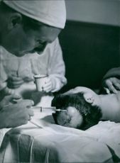 Doctor injecting an injection in the head of a patient.