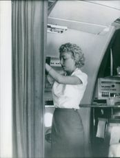 1959  A photo of an air hostess standing in the airplane checking something.
