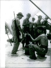 Soldiers are charging their guns and weapons. 1961