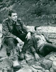 Robert Hossein sitting on rock with a man.