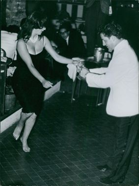 Man and woman dancing in a party, people looking at them.