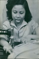 Woman stitching clothes on sewing machine.