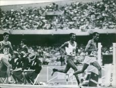 Athletes running in competition in stadium.