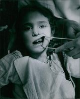 First step in preparing mouth for a space retainer is grinding adjoining teeth. This operation, here being performed on a 7 year old, is painless. Space retainer prevents adjacent teeth from sliding into space where baby or foundation tooth used to be thu