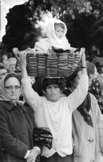 Woman carrying a child in basket, numerous people standing around.