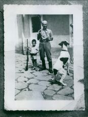 Vintage photo of a man and child holding guns with dog  jumping. Jant.