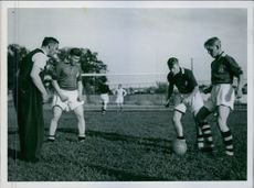 A photo of four men playing football.