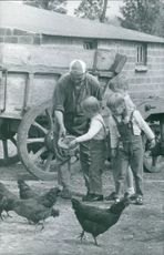 Prince Albert II`s children taking grain to feed chickens.