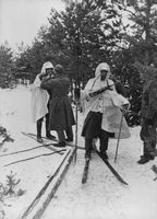 Soldiers with their guns and skiing on the snow.