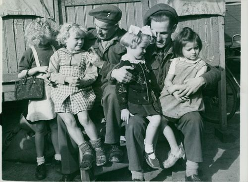 Entertainment as re-education. Gnr. Charles Offler R.A., whose home is Nottingham, left with Pte. Duncan Livingstone, P.C., who comes from Edinburgh are reminded of home as they make friends with these bonny German children at the fun-fair.