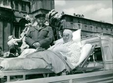 Scene from a movie,  Maurice Chevalier lying on stretcher.