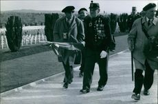 An officer walking with a man talking and holding a flag , 1966.