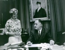 Marcilhacy sitting in his office instructing his secretary. 1965