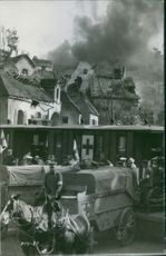 Burning houses after blast, and medical team gathered outside their camp.