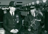 A policeman armed with an SAS-style sub-machine gun patrolling one of the passenger terminals at Heathrow airport, accompanied by a conventional policeman. 1986.
