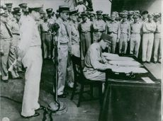 A military officer signing something on the table.
