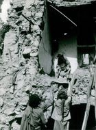 People helping the child get down from the damaged building in Yemen, 1963.