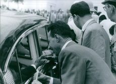 People greeting and hand shaking to a man siting in the car.