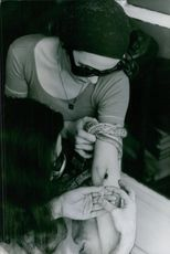 Woman injecting injection in another woman's hand. 1973