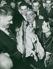 Anton Geesink in a party with people around him as he open a gift.  Taken - 11 Dec. 1961