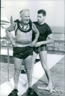 A man is helping to politician Gaston Defferre to open the swimming costume after diving