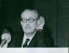 A photo of a British Conservative politician and statesman who served as the Prime Minister of the United Kingdom from 10 January 1957 to 18 October 1963 Maurice Harold Macmillan trying to listen.