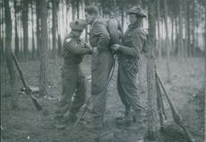 Two riflemen helping a fellow soldier to wear his flame-thrower.