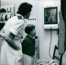 Woman with child looking at display.