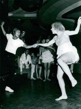 """A man and a woman enjoying themselves as they dance together at """"The Titan Club"""" in Rome, Italy."""