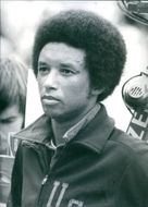 Tennis player Arthur Ashe looking at something.