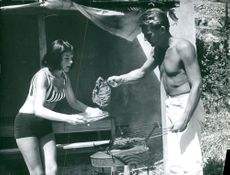 Couple cooking outdoor on sunny day.
