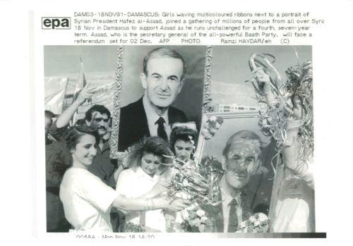 Girls waving multicolored ribbons next to a portrait of President Hafez al-Assad.