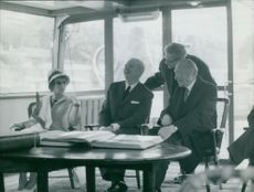 Konrad Adenauer sitting with people, laughing.