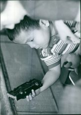 A little boy playing wit toy car.