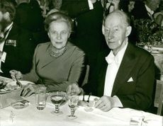 Eyvind Johnson sitting with a woman on table.