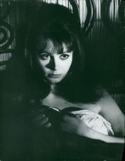 Sarah Miles is lying on bed.