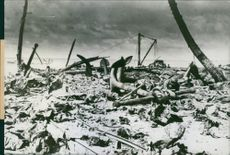 A U.S. Coast Guardsman examines huge old-fashioned anchors found amidst the debris on a beach at Kwajalein.