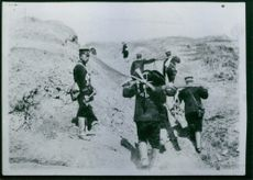 Soldiers walking, holding and taking away a weapon.