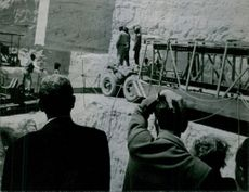 A rear view of André Malraux, watching a trailer being pulled.